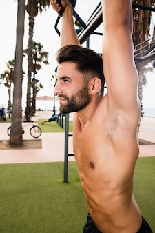 Sideways handsome sportive male exercising