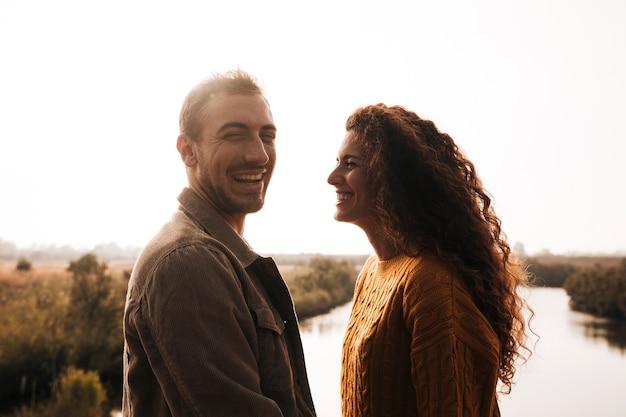 Sideways happy couple next to a lake
