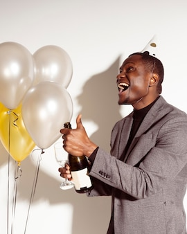 Sideways happy man opening a bottle of champagne