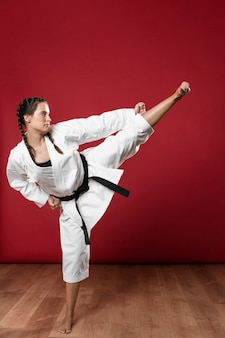 Sideways karate woman in traditional white kimono on red background