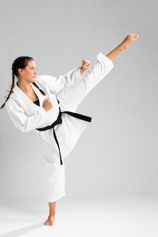 Sideways karate woman in traditional white kimono on white background