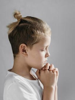 Piccolo ragazzo biondo di lato che prega