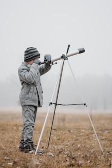 Маленький мальчик боком с помощью телескопа