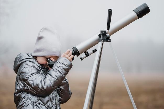 망원경을 사용 하여 옆으로 어린 소녀