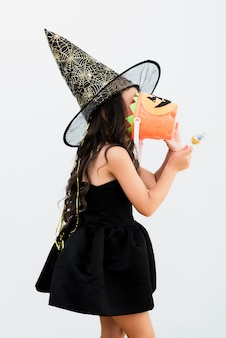 Sideways little girl in witch costume for halloween