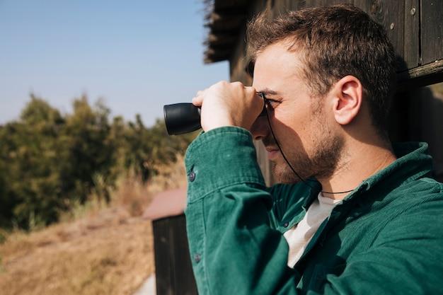 Sideways man looking through binoculars Free Photo