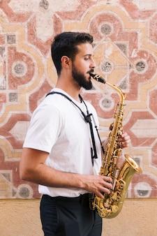 Sideways man medium shot playing the saxophone with geometric background