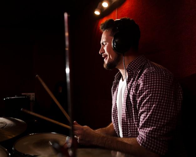 Боком человек играет на барабанах и в наушниках