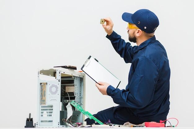 Sideways man repairing a computer