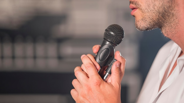 Sideways man singing at microphone