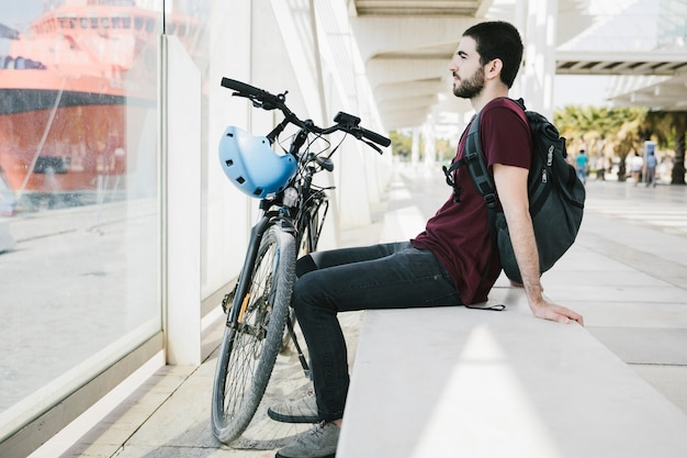Sideways man sitting next to bicycle