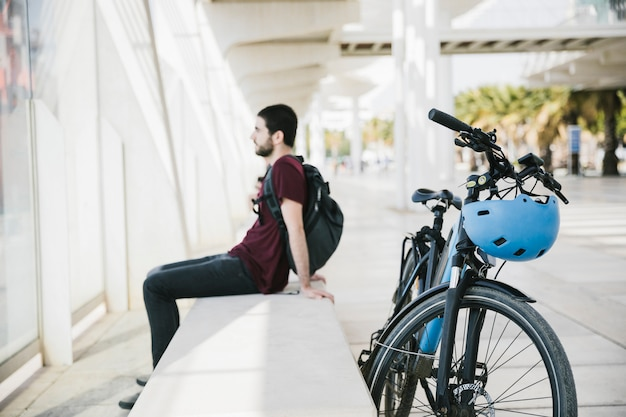 Sideways man sitting next to electric bicycle