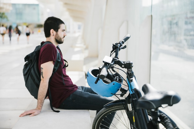 Sideways man sitting next to electric bicycle