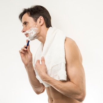 Sideways of man  standing andshaving