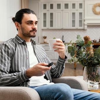 Sideways man watching tv and eating popcorn