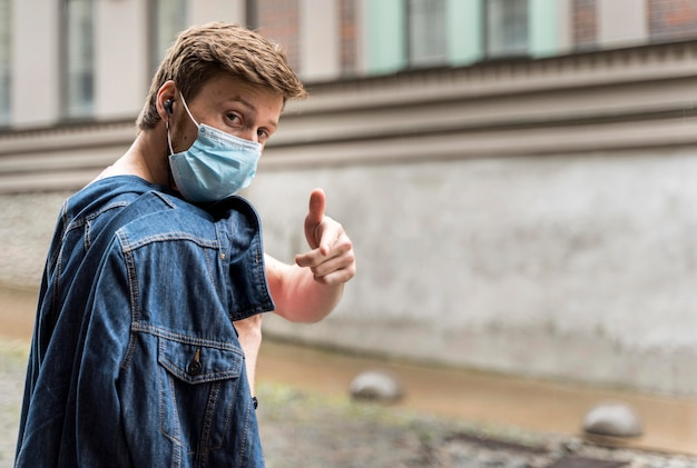 Uomo di lato che indossa una mascherina medica all'esterno con lo spazio della copia