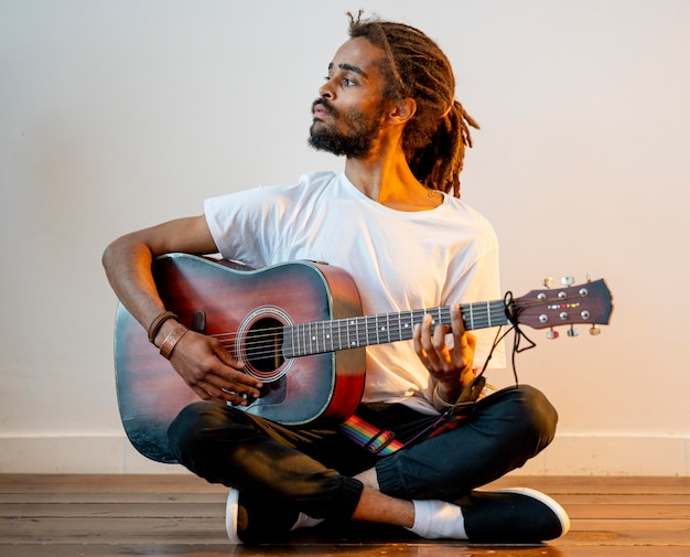 Боком человек с боязнями играет на гитаре