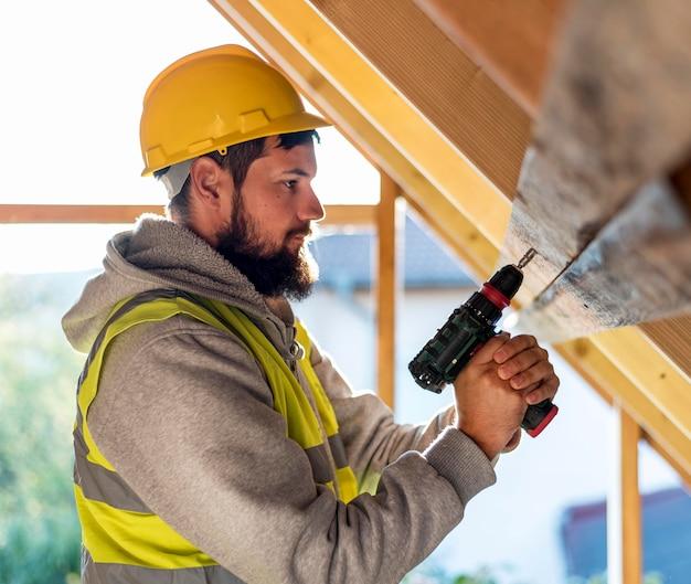 屋根に取り組んでいる横向きの男