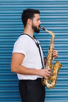 Sideways medium shot man playing the saxophone
