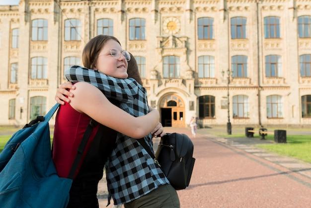 Боковой средний снимок двух девочек-подростков, обнимающих