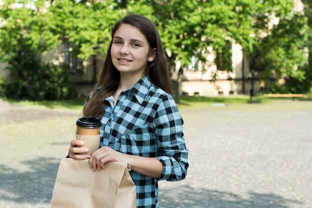 Sideways medium shot of teenage girl holding papercup and lunch bag