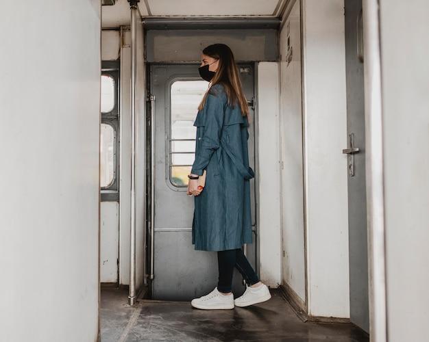 Боком пассажир в поезде стоит