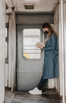 Sideways passenger in the train reading