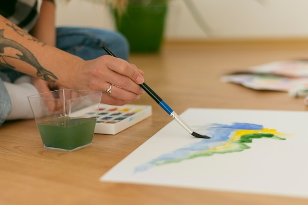 横向きの人が床に座って絵の具を塗る