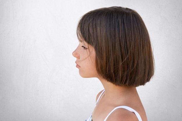 Ritratto laterale della ragazza lentigginosa adorabile che esamina distanza mentre avendo espressione vaga isolata sul muro di cemento bianco. bambina con i capelli corti scuri in piedi lateralmente con sguardo serio