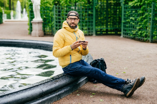 Sideways portrait of bearded male dressed in casual clothes wearing eyeglasses holding smartphone typing something