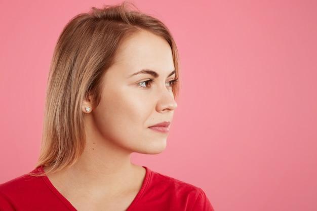 Sideways portrait of blonde beautiful young female model looks pensively aside