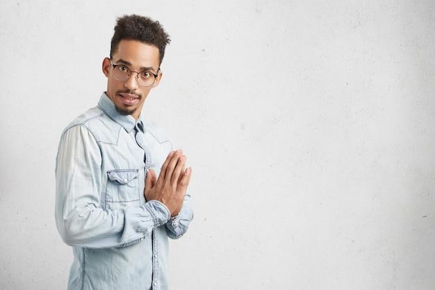 Ritratto laterale di uomo fiducioso con capelli ricci, viso ovale, indossa una camicia di jeans