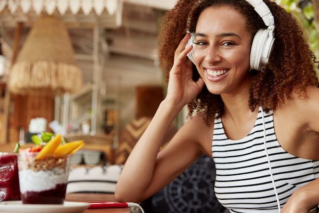 Sideways portrait of dark skinned female with dark hair uses high quality headphones and mobile phone for listening music or audio book, spends leisure time at cafe, enjoys high speed internet
