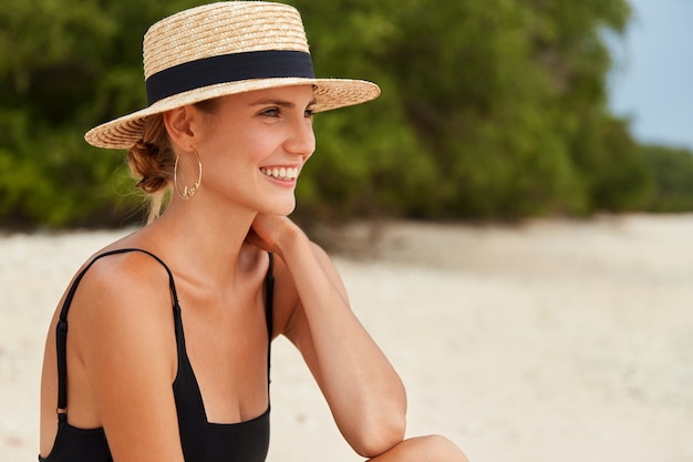 Sideways portrait of happy dreamy woman looks away on ocean as sits on tropical beach, wears summer hat, has hair tied in knot, has harmony and relaxation. female wears bikini admires marine view