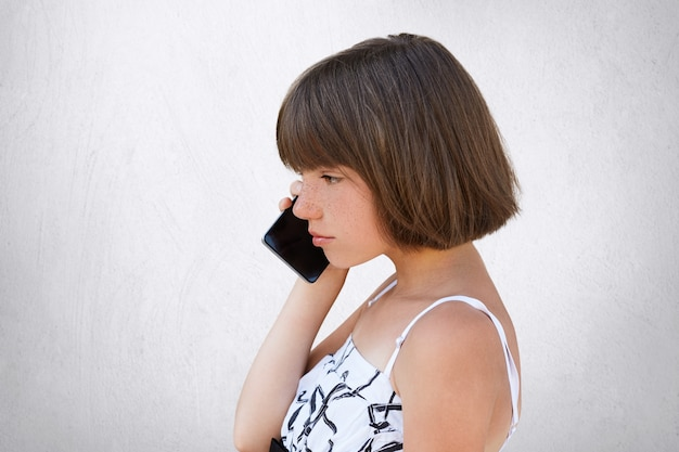 Sideways portrait of little girl with bobbed hair, wearing white dress, speaking on cell phone with serious expression. stylish female kid posing in studio with modern gadget, isolated on white