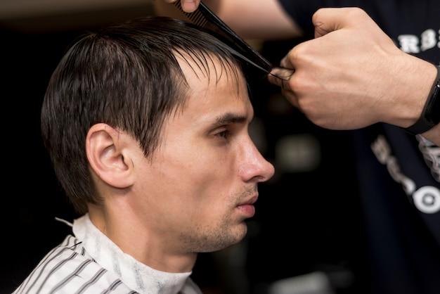 Sideways portrait of a man getting a haircut