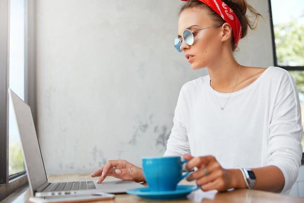 Боковой портрет сосредоточенной молодой красивой девушки-графического дизайнера в модных тонах, работает за современным ноутбуком и пьет кофе, проводит обеденный перерыв в кафетерии, готовит проектную работу.