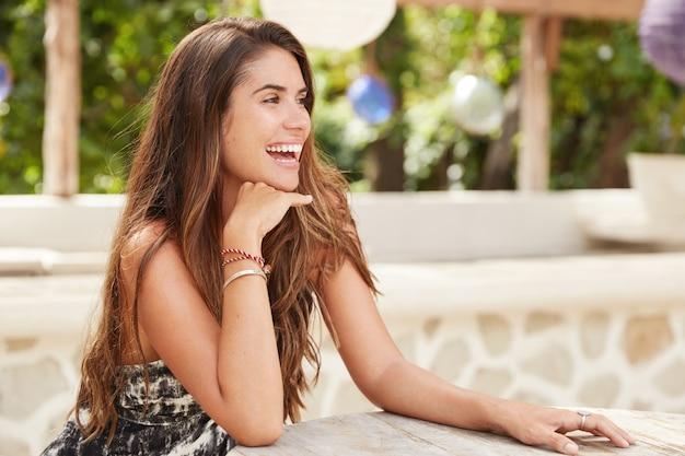 Боковой портрет счастливой девушки-модели радостно смотрит вдаль, в приподнятом настроении, носит модную одежду, отдыхает в летнем кафетерии, наслаждается летним отдыхом. люди и концепция досуга