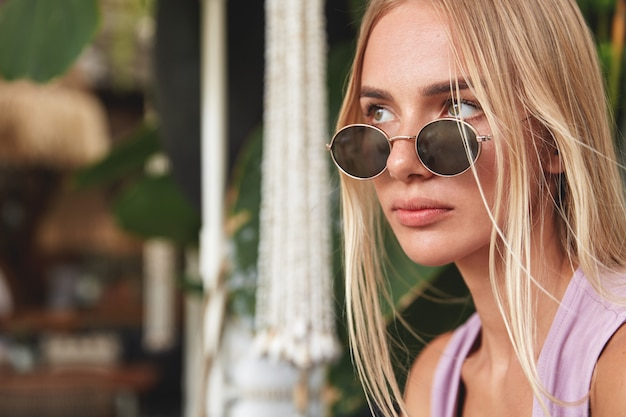 Sideways portrait of thoughtful stylish hipster girl in trendy sunglasses, looks pensively away, contemplates about future plans. beautiful blonde woman being deep in thoughts. people, style concept