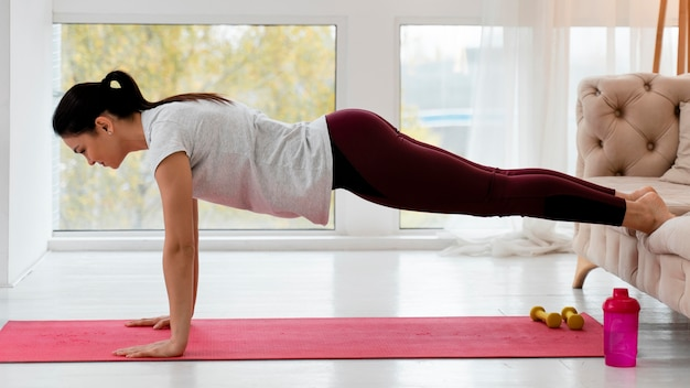 Sideways pregnant woman doing yoga at home
