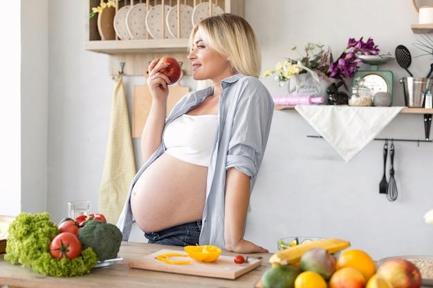 Боком беременная женщина ест яблоко