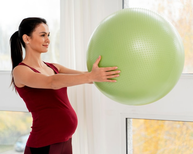 녹색 피트 니스 공을 들고 옆으로 임신 한 여자