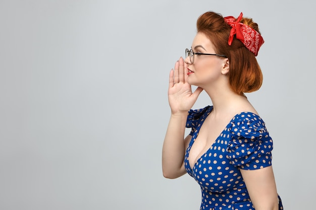 Sideways profile of attractive stylish young lady in vintage clothes calling someone, whispering secret or gossip, keeping hand at her mouth, posing at blank wall with copy space for your content