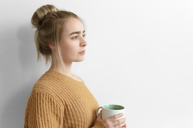 Боком серьезная задумчивая молодая женщина с грязной прической держит большую кружку, пьет горячее какао дома, стоя у глухой стены