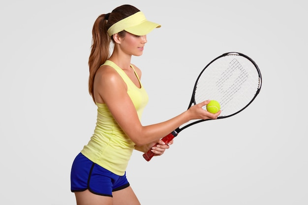 Sideways shot of active healthy tennis player going to put in first service, uses special equipment for game, shows her abilities, stands against white wall, wears t shirt, cap and shorts
