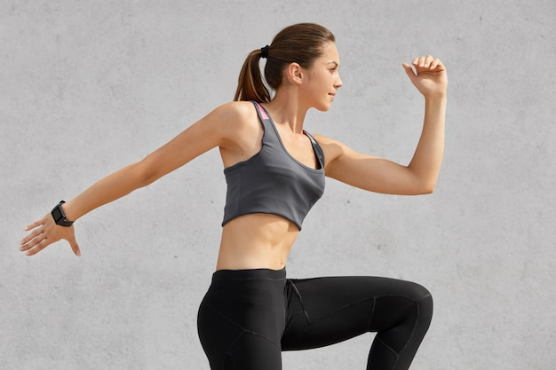 Sideways shot of active woman being in motion, has pony tail, wears sports clothes, poses against grey