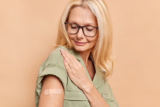 Sideways shot of adult woman with fair hair looks attentively at arm with plaster after vaccine injection protects herself from coronavirus wears spectacles and dress isolated over beige wall