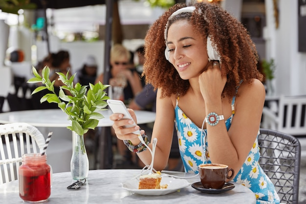 Sideways shot of attractive curly woman has happy expression, enjoys electronic song in modern headphones, has recreation time, reads text message on cell phone