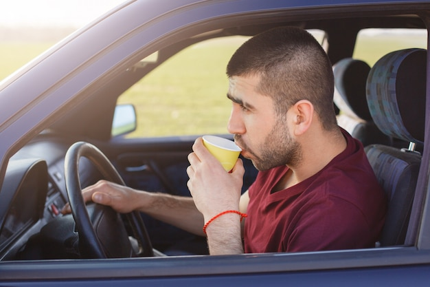 Sideways shot of attractive male driver stops to have break after driving, drinks hot coffee, looks thoughtfully