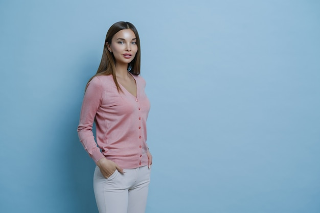 Sideways shot of beautiful dark haired young european woman wears stylish jumper, keeps hands in pocket of white trousers